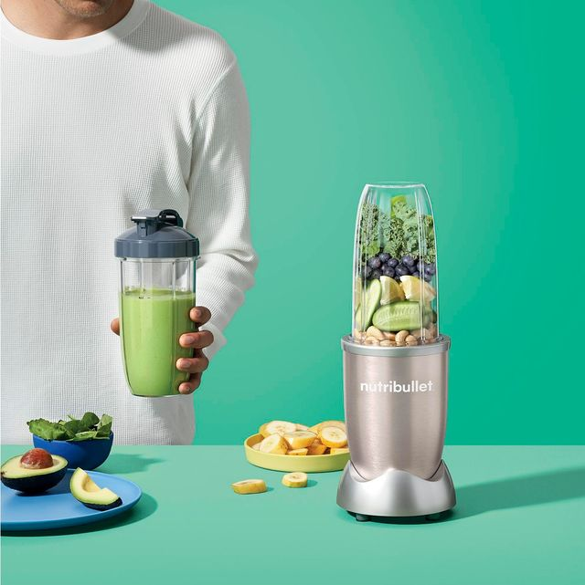 a male model blending up smoothies with fruits and vegetables