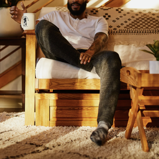 a model wearing sweatpants on a couch