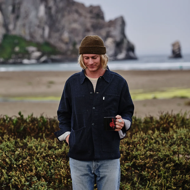 a guy drinking coffee at the beach