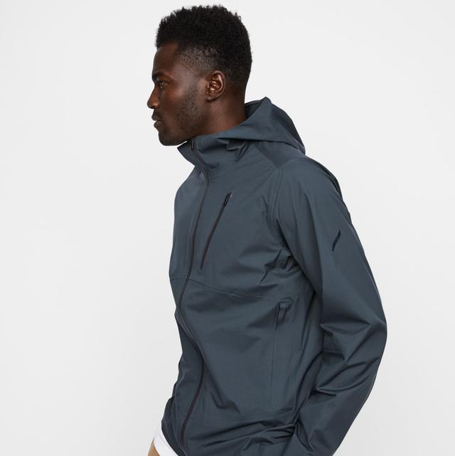 a model wearing a gray rain jacket