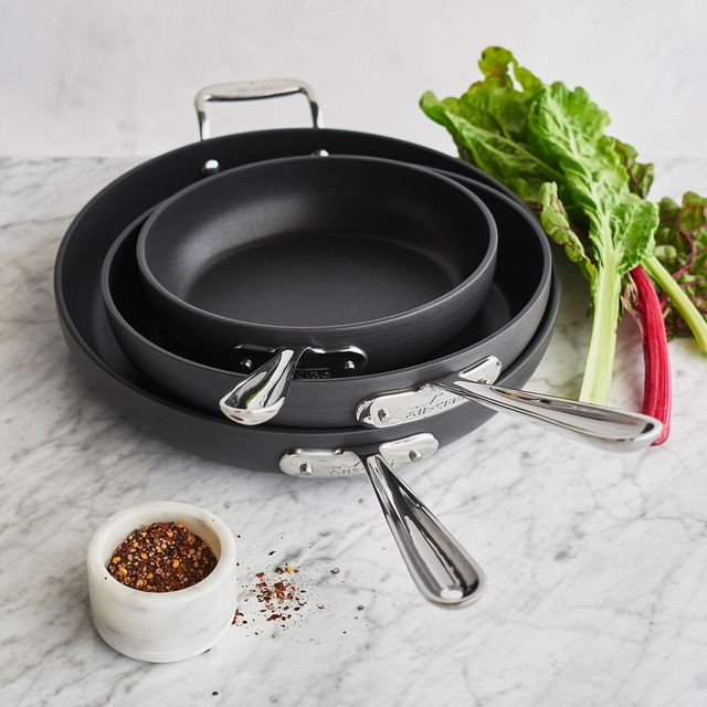three skillets and some cooking ingredients