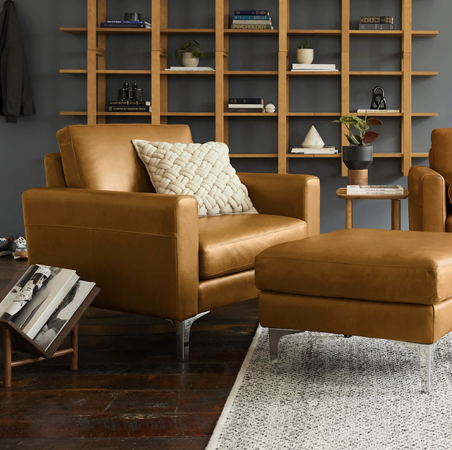 a living room scene with brown leather couch, chair and ottoman