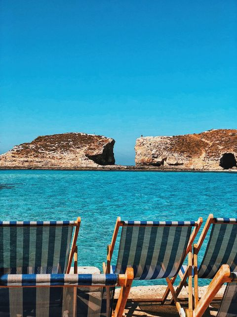 Deck Chairs On Rocks By Sea Against Clear Blue Sky