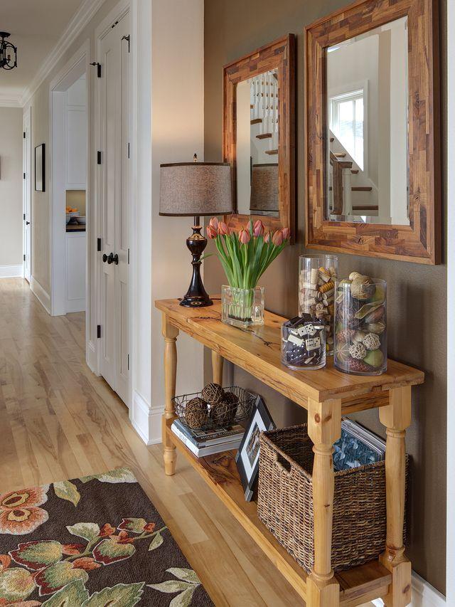 recibidor de una casa con mesa, espejos, cestos, flores, objetos de decoración y una lámpara