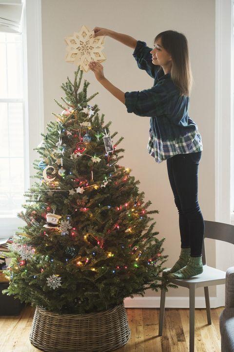 woman placing star on top of christmas tree