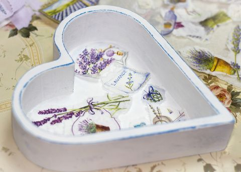 Boîte en bois blanche en forme de coeur avec des images de lavande de découpage sur le fond et du papier découpé autour d'elle