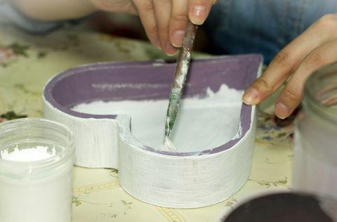 Mains peignant l'intérieur d'une boîte en bois en forme de coeur violet blanc