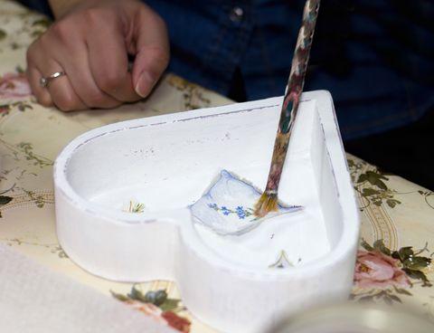 La main d'un artisan peignant une image découpée avec de la colle à l'intérieur d'une boîte blanche en forme de cœur