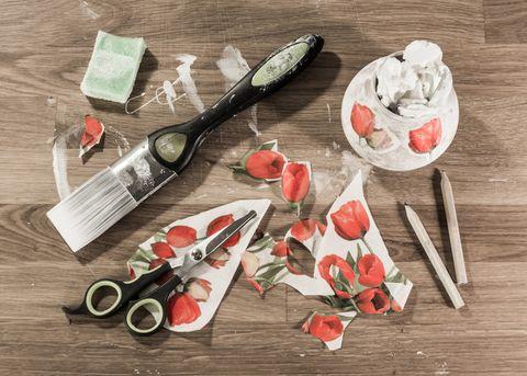 Outils de découpage sur table en bois, y compris une brosse, des ciseaux, des crayons, une éponge et du papier découpé
