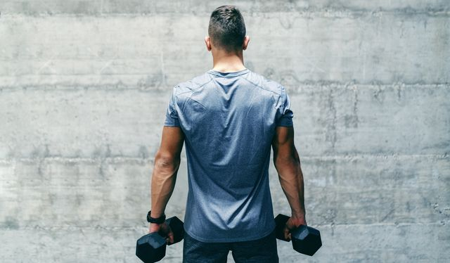 dedicated bodybuilder in sportswear standing in front of the wall and holding dumbbells in hands, backs turned
