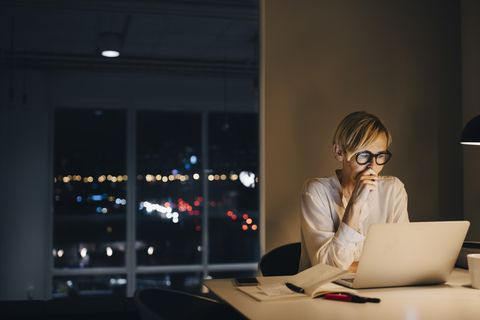 dedicated mature businesswoman using laptop while sitting at illuminated desk in coworking space