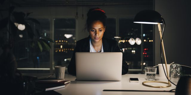 dedicated young businesswoman working late while using laptop at creative office