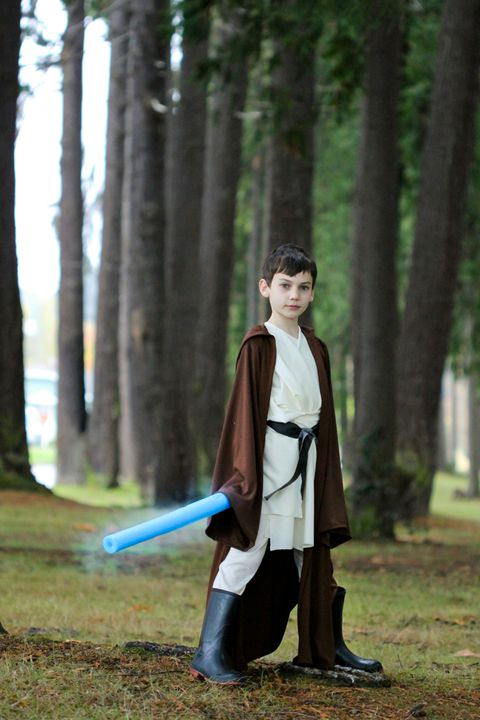 boy standing outside dressed as obi wan with blue pool noodle as light saber and long brown robe