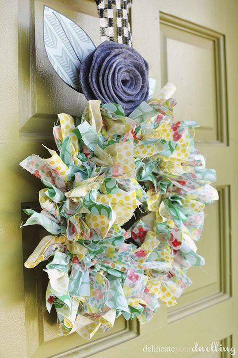 colorful wreath made of fabric strips with blue fabric rose on top hanging from olive green front door