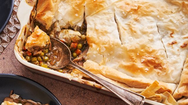 saucy vegan mushroom pot pie with phyllo dough crust, first portion scooped onto a plate