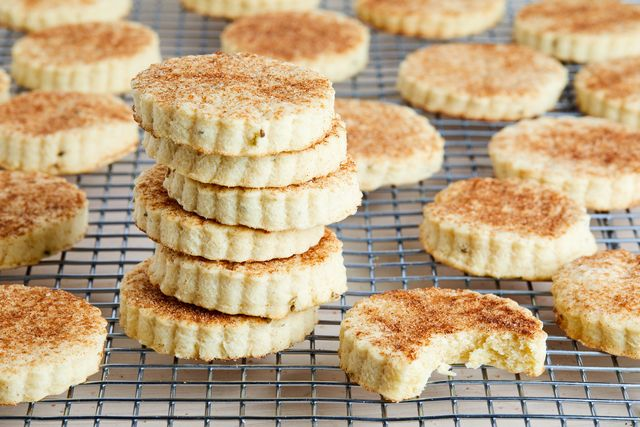 biscochitos stacked in a cutting rack, with fluted edges, topped with cinnamon sugar some anise seeds are visible in the cookies