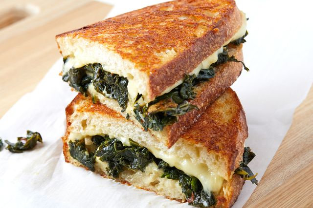 grilled cheese cut in half, loaded with melty white cheese and braised kale