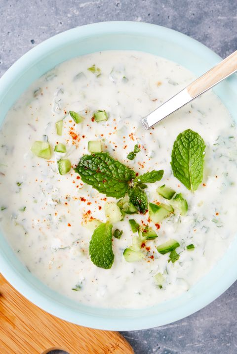 raita in a bowl with cucumbers, mint, and powdered red spice cutting board with mint and cucumbers alongside