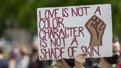 sign reading 'love is not a color character is not a shade of skin'