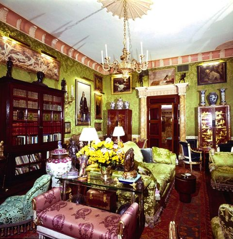 vogue, february 01, 1977   a reverse view of the living room of the upper east side, new york, new york, apartment of robert denning and vincent fourcade, owners of the interior designer firm denning  fourcade, inc the style of the 40 long x 25 wide x 15 tall ornate room is described as a louis seize european palais it includes green silk damask walls, a brass chandelier, green and white brocade satin upholstered furniture, a large wooden bookcase with glass paned doors, multiple paintings hung all over the walls, marble columns framing the doorway, and a large red oriental rug horst p horstconde nast via getty images