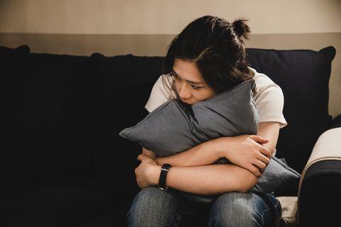 depressed asian woman sitting on sofa holding a cushion