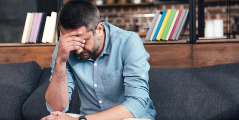 depressed man with hand on forehead sitting on sofa in psychiatrist office