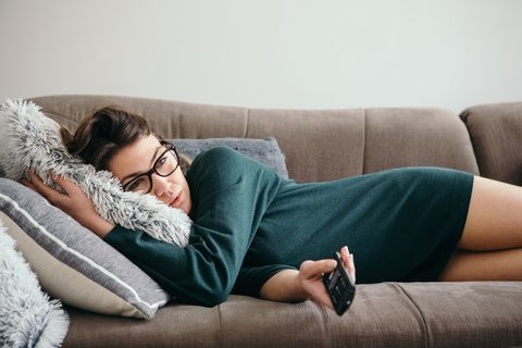 depressed woman changing channels on a tv remote