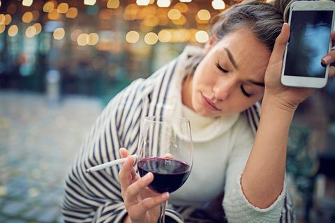 depressed woman is drinking wine and holding her broken phone in a rainy day