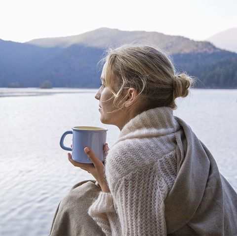 young woman wrapped in blanket holding coffee cup