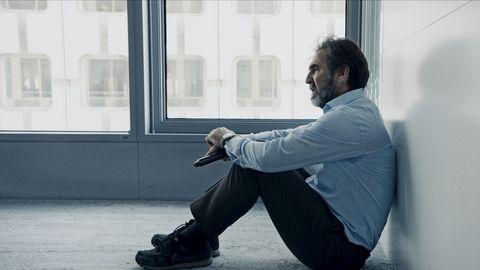 eric cantona apoyado en una pared sentado en el suelo en la serie derapages