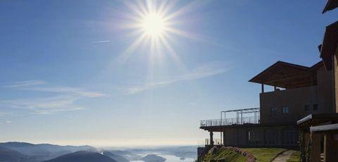 Sky, Mountain, Light, Natural landscape, Mountain range, Cloud, Sunlight, Hill station, House, Atmosphere,