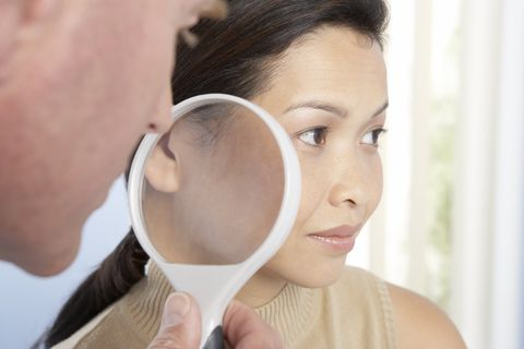Dermatologist using magnifying glass to examine woman's skin