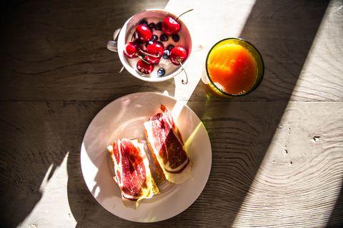 imagen de un bodegón de desayuno a base de zumo de naranja, tostadas de jamón y leche con frutas