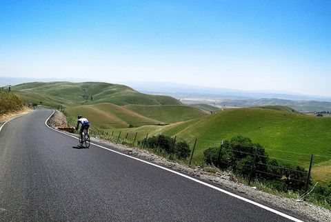 cyclist descending road in hilly green countryside