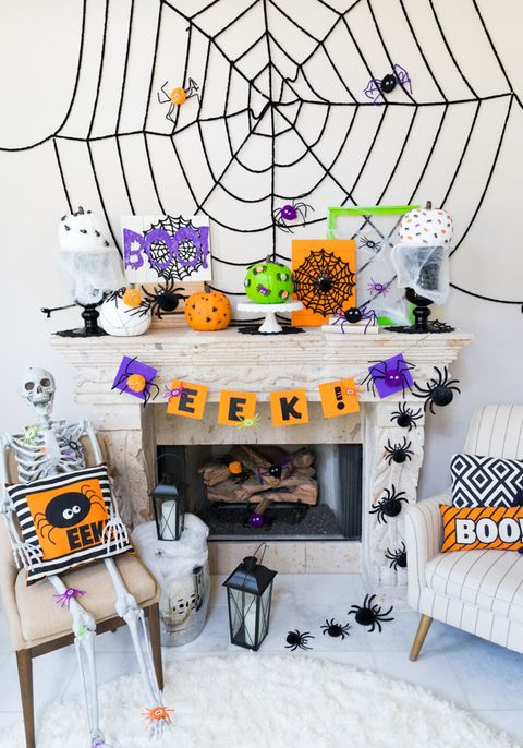"there is a white fireplace with two chairs beside it, with halloween spiders crawling up one side, a banner across the mantel that reads ""eek,"" and a black yarn web with pom pom spiders in it on the wall above there are spider decorated pumpkins on the mantel and a skeleton sitting in one of the chairs holding a pillow with the word ""eek"" on it and a picture of a cute, cartoon spider"