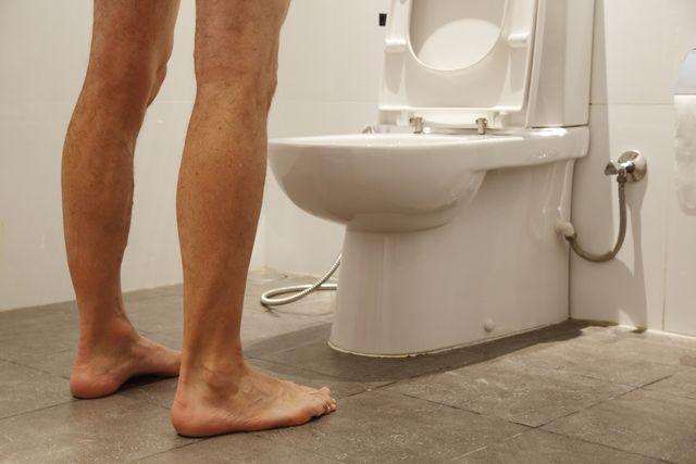 un hombre con las piernas desnudas mea de pie frente a una taza del vater en mitad de la noche