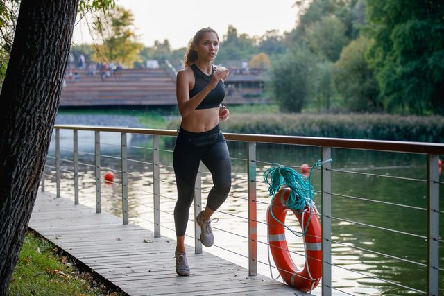 determinated female athlete running through city park