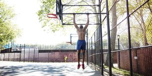 Determined athlete doing chin-up on basket ball hoop