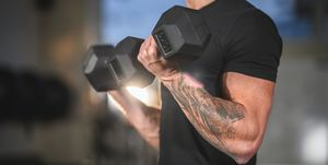 Determined Caucasian Male Athlete Working Out with Dumbbells
