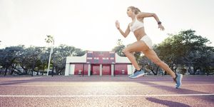 Determined female athlete running on race track