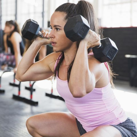 Determined, muscular young woman doing squats with dumbbells in gym
