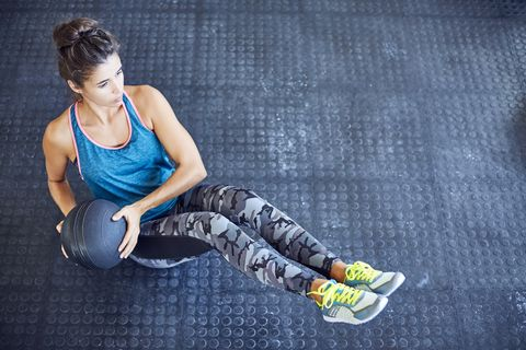 determined woman exercising with medicine ball on gym floor