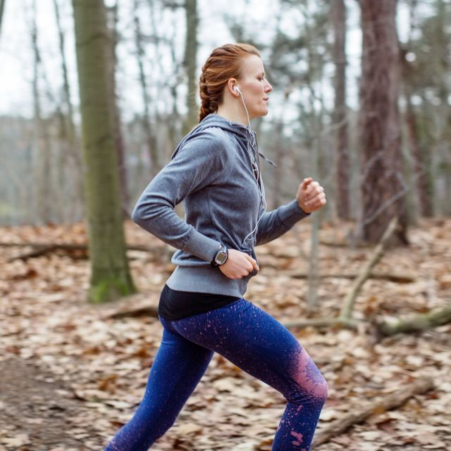 determined woman jogging in forest
