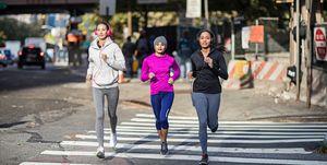 Determined young women jogging on crosswalk