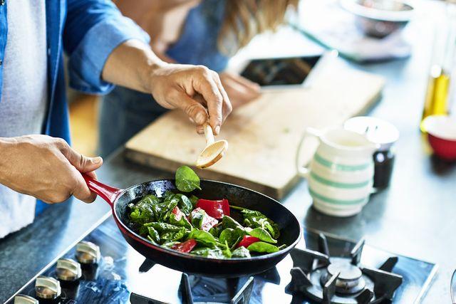 close up van man die pan met groente en een houten lepel vasthoudt