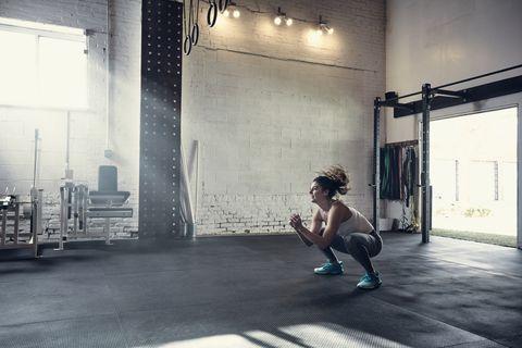 vrouw in de sportschool doetsquat jacks