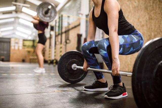 vrouw tilt barbell op om deadlift uit te voeren in sportschool