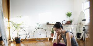 Vrouw kijkt op telefoon op yogamat