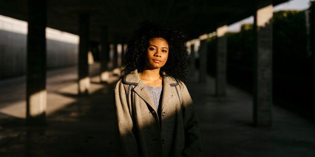jonge zwarte vrouw in een donkere parkeergarage kijkt in de camera
