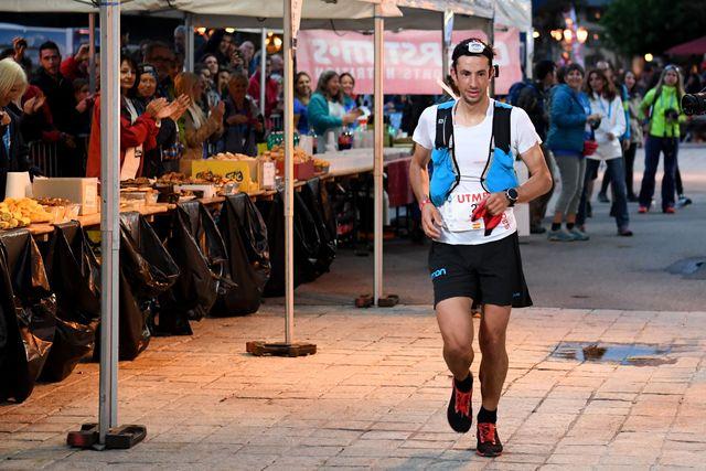 el corredor español de montaña kilian jornet corre por delante de un avituallamiento en al utmb